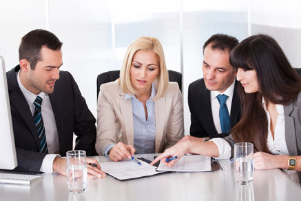 Several Men and Women Wearing Business Attire Looking at a Paper