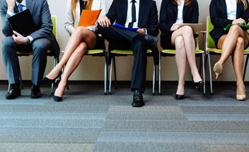Men and Women in Business Attire Sitting in a Row