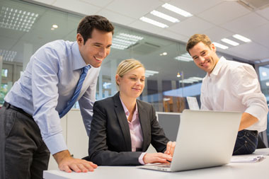 Two Men and One Woman in Business Attire Smiling and Looking at a Laptop